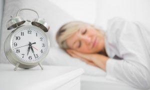 Wecker und schlafende ältere Dame