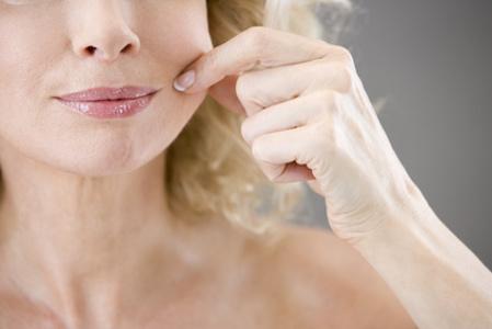 Dame untersucht Spannkraft der Haut