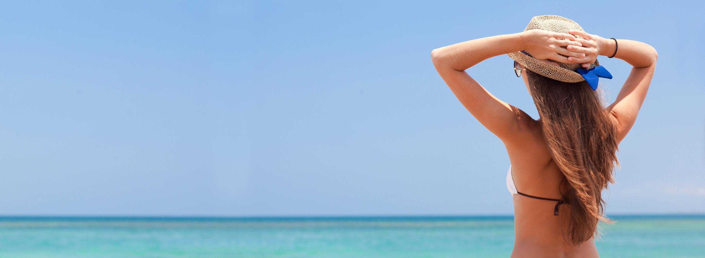 Frau im Bikini am Meer mit Sonnenschein